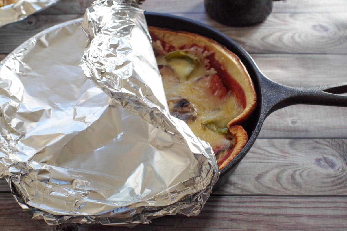 cast iron pizza with foil pulled back on top