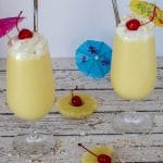 2 health pina colada drinks on a white faux wood surface, with pineapple, maraschino cherries and umbrellas