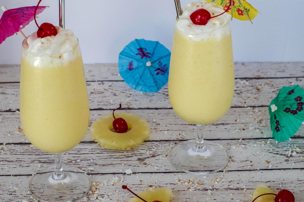 2 healthy pina colada drinks on a white faux wood surface, with pineapple, maraschino cherries and umbrellas