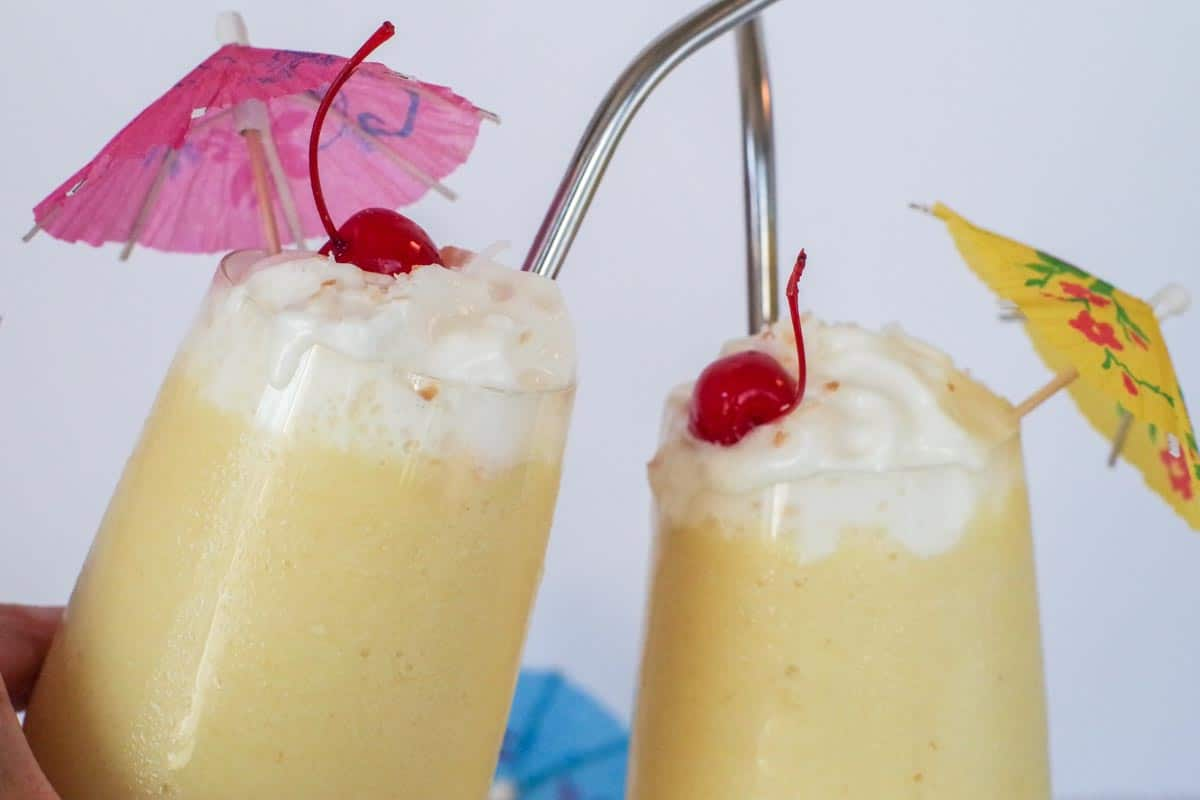 2 healthy Pina Colada glasses clinking together
