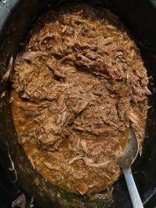 shredded beef in sauce in slow cooker