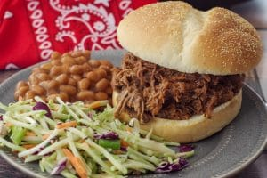 beef on a bun on a grey plate with coleslaw and beans