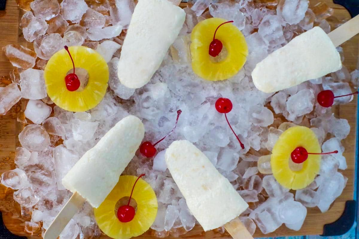 pina colada popsicles on a bed of ice with pineapple and cherries