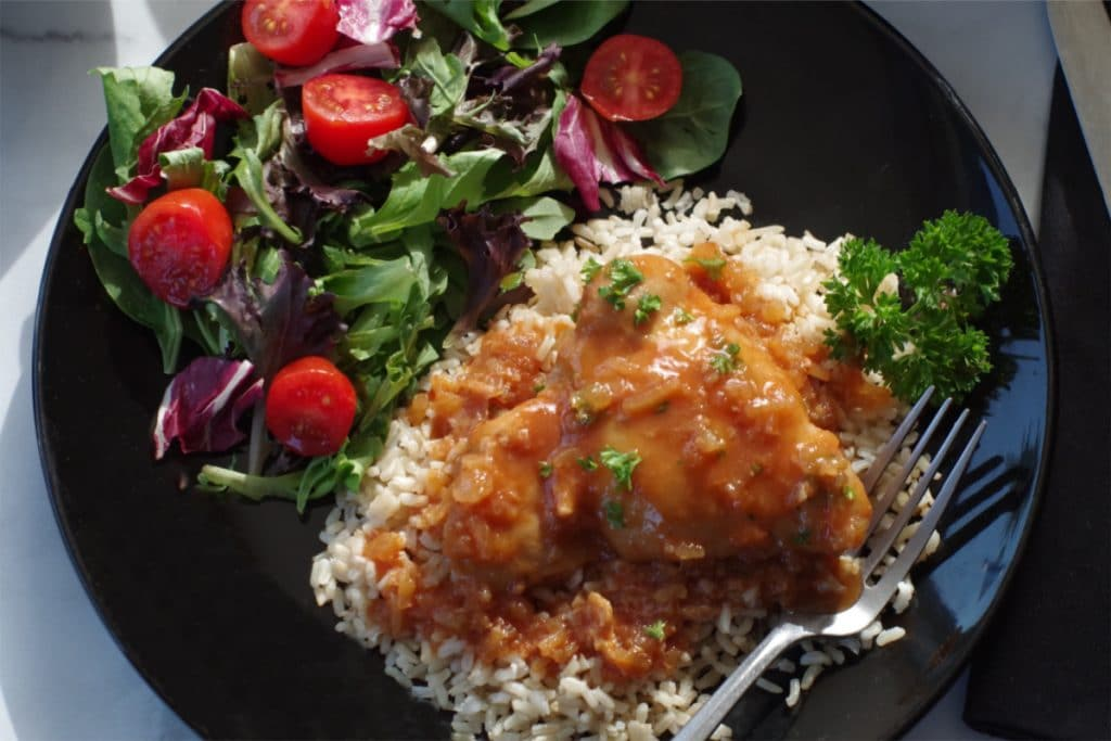 Chicken in a Hurry on a bed of rice, with spring mix salad, on a black plate with a fork