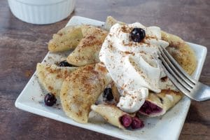 Saskatoon berry dessert pierogies on a white plate with a fork