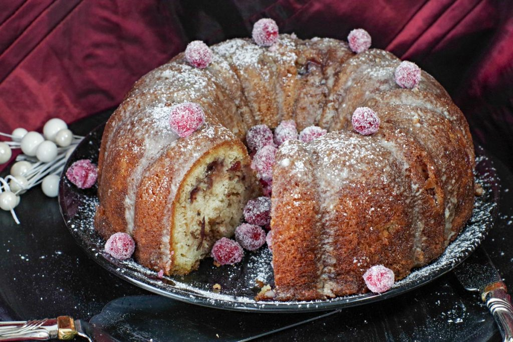 whole cranberry coffee cake with piece missing and candied cranberries in the space where the piece is missing
