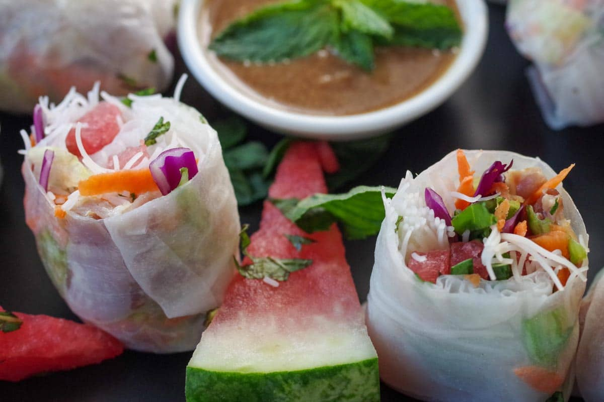 salad rolls with watermelon and prosciutto, sliced in half, with wedge of watermelon and dip in the background