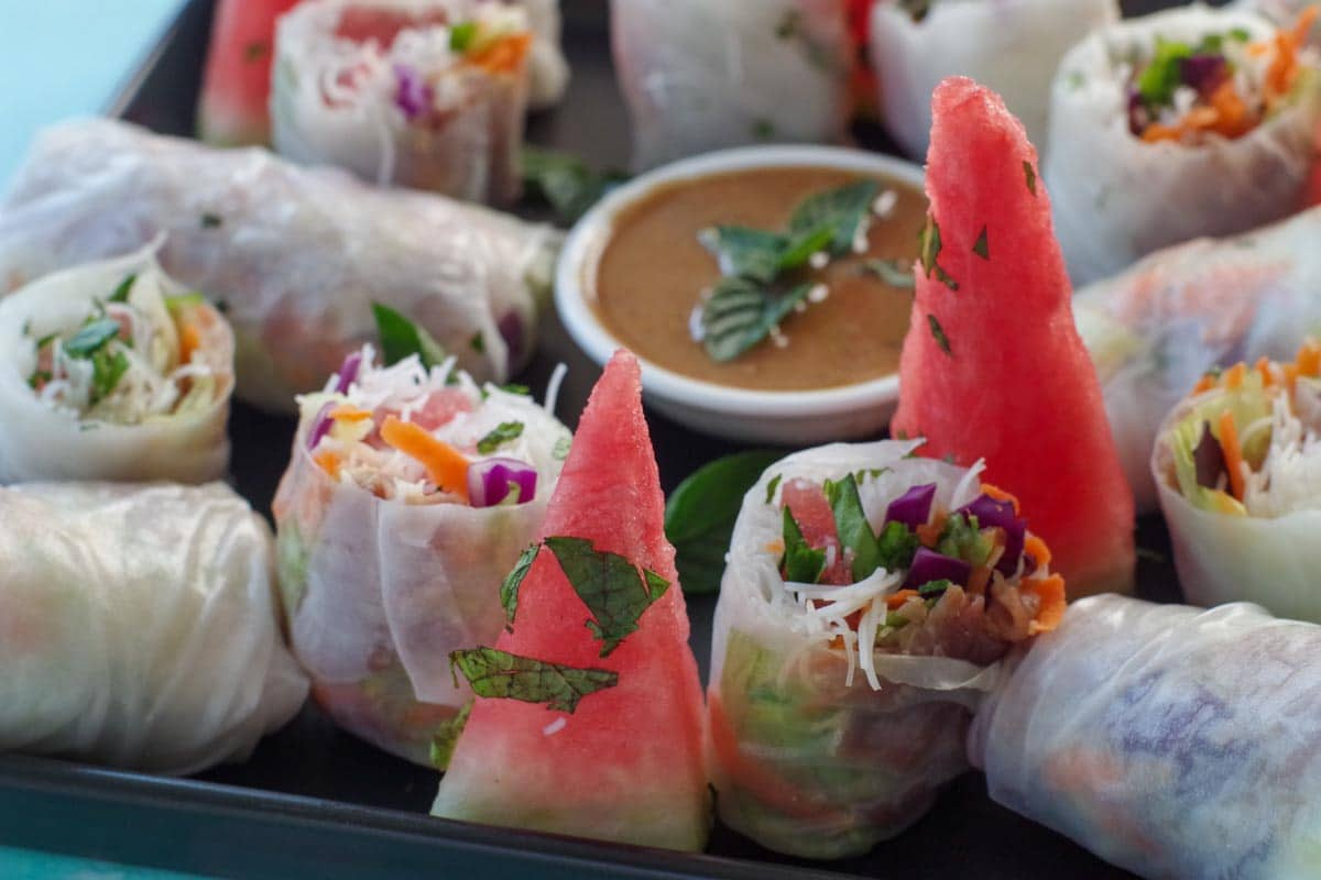 salad rolls on a platter, some cut, others whole with dip and wedges of watermelon, sprinkled with fresh mint