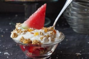 watermelon breakfast parfait in a glass bowl with spoon sticking out and more glass bowls in the backgroun