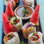 Watermelon Prosciutto Salad rolls, cut in half, on a black platter, with wedges of watermelon