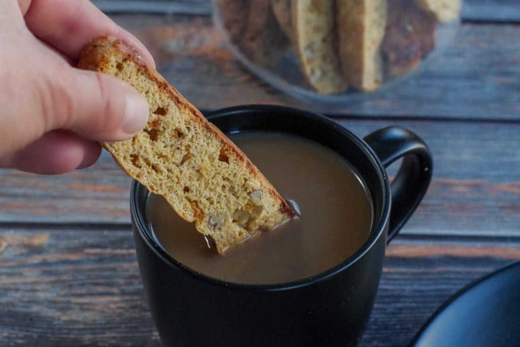 healthy biscotti being dipped into a cup of coffee