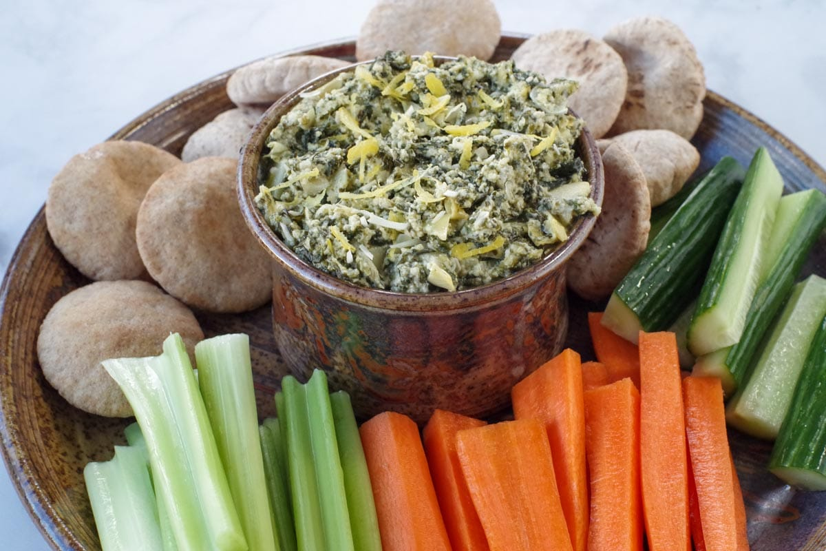 healthy spinach artichoke dip in a ceramic bowl on a platter with vegetables and mini pita breads