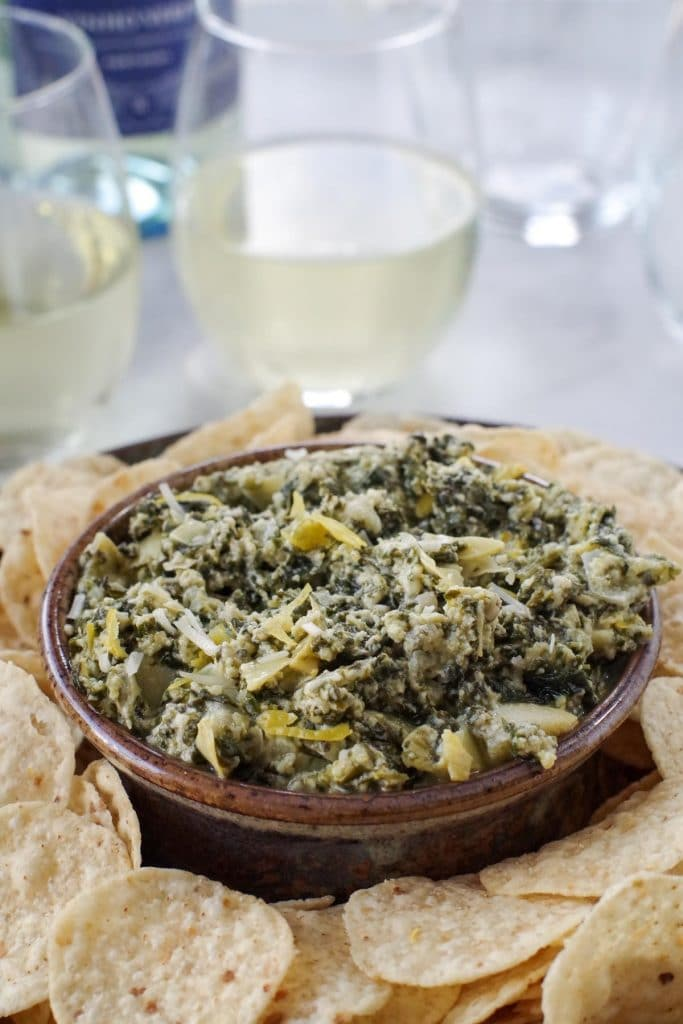 spinach artichoke dip on a platter with glasses of wine in the background
