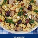 Pinterest pin with white text on blue background on the bottom and photo of bowl of Mediterranean pasta on top