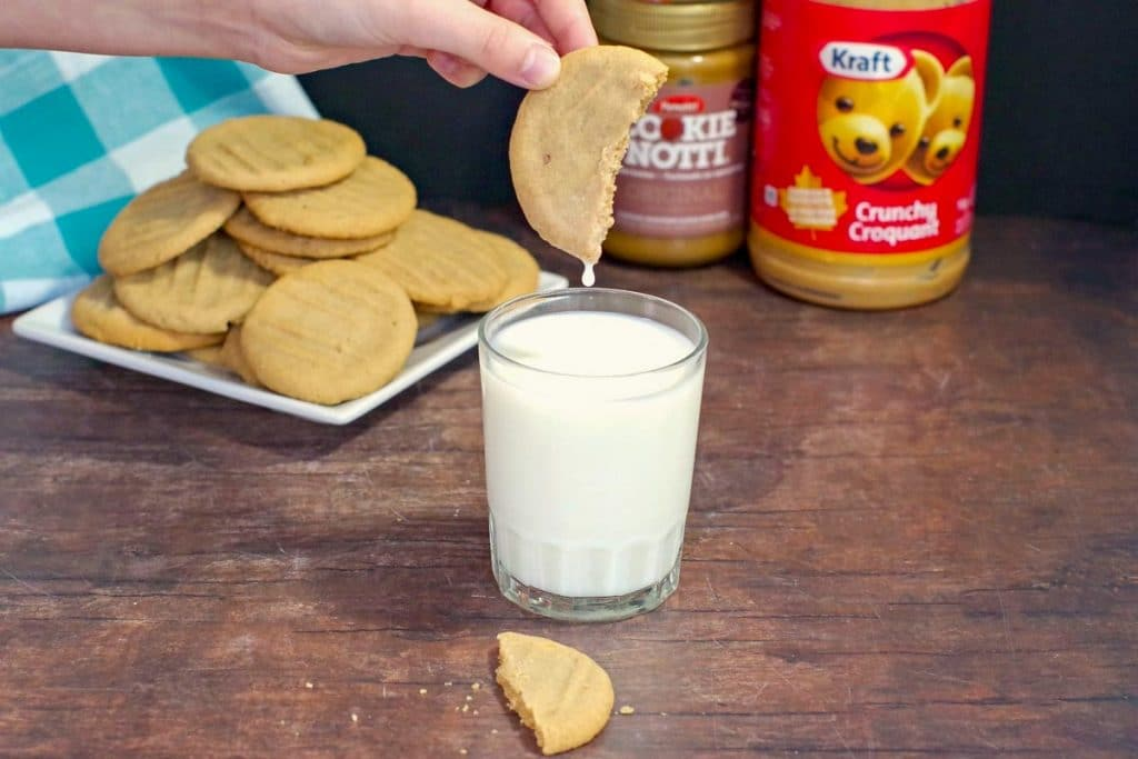 cookie butter cookie being dipped into a glass of milk