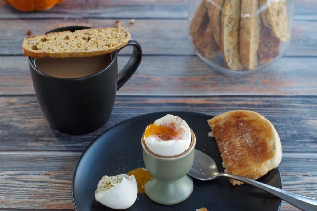 pumpkin pecan biscotti on top of a cup of coffee, with a boiled egg, with toast on a plate in front