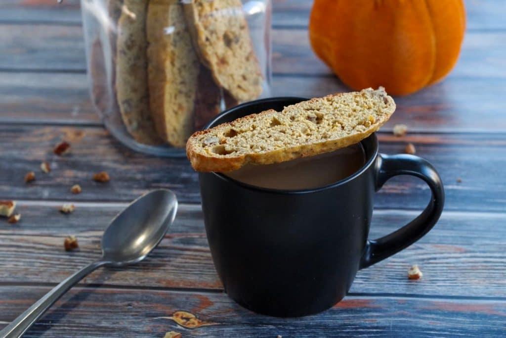 pumpkin spice biscotti on a black mug with a jar of pumpkin biscotti in the background