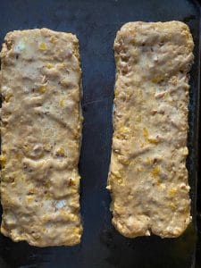 biscotti shaped into logs on baking sheet with egg wash brushed on