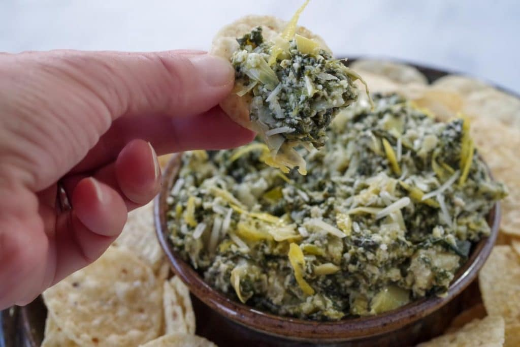 spinach artichoke dip being held up on a chip over a platter of more dip and tortilla chips
