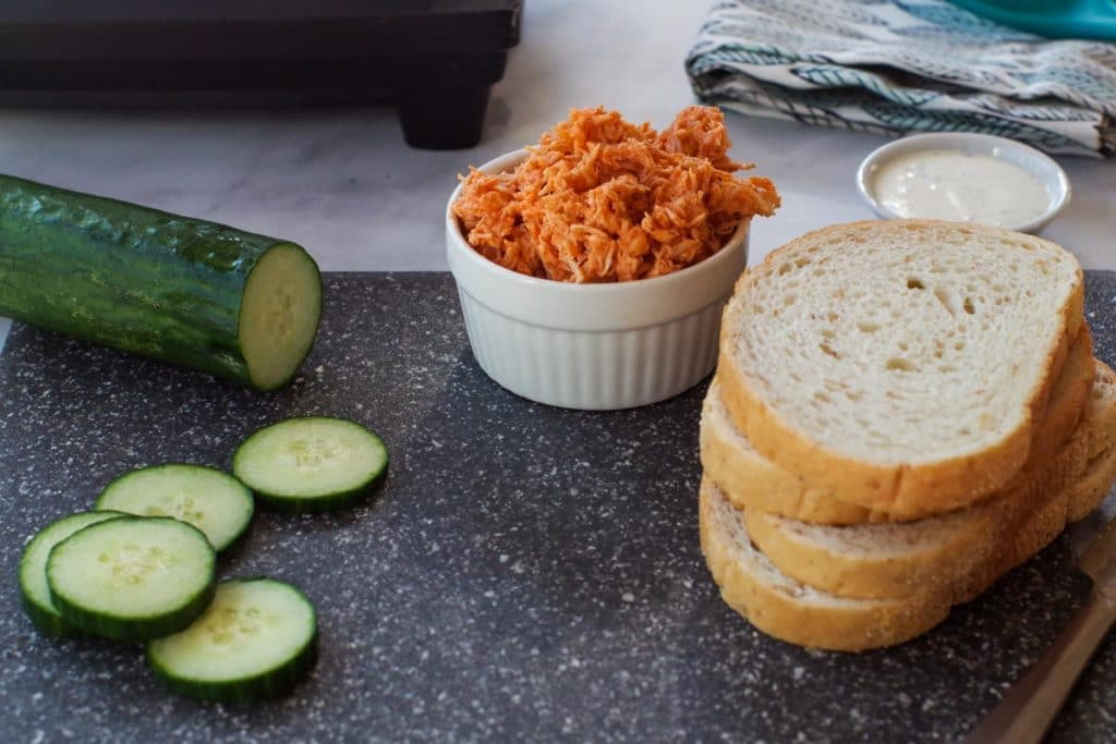 ingredients for buffalo chicken panini- bread, cucumbers, ranch dip and buffalo chicken on cutting board