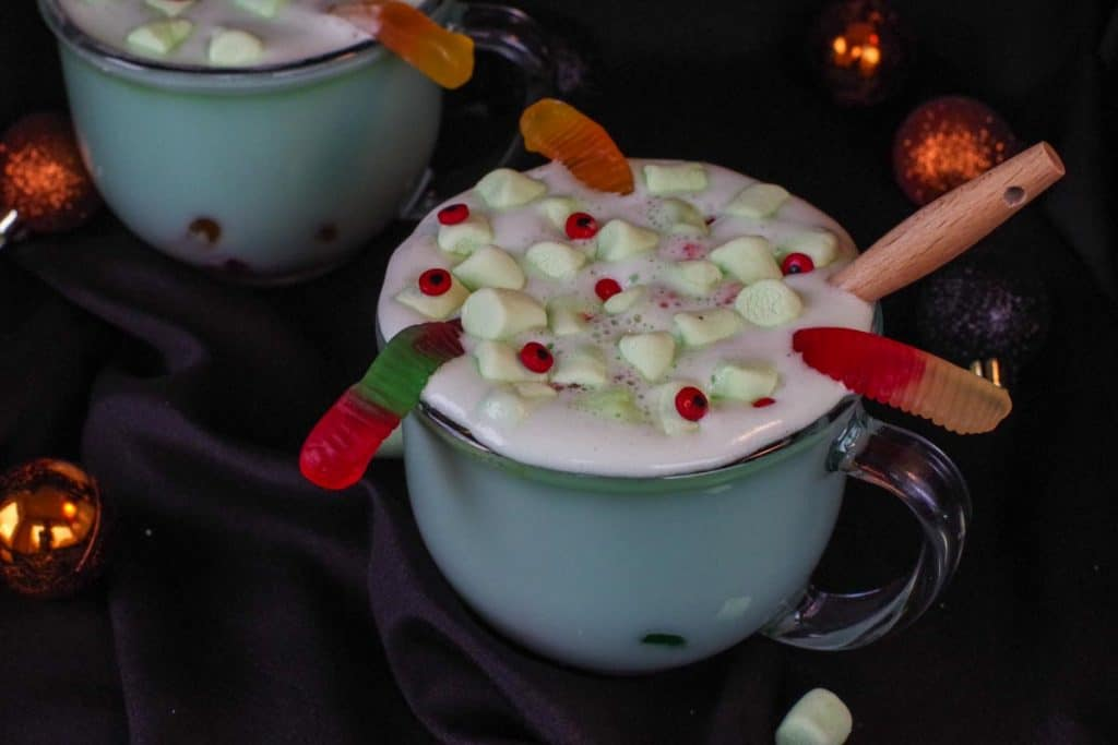 Halloween hot chocolate in a clear mug with a black background