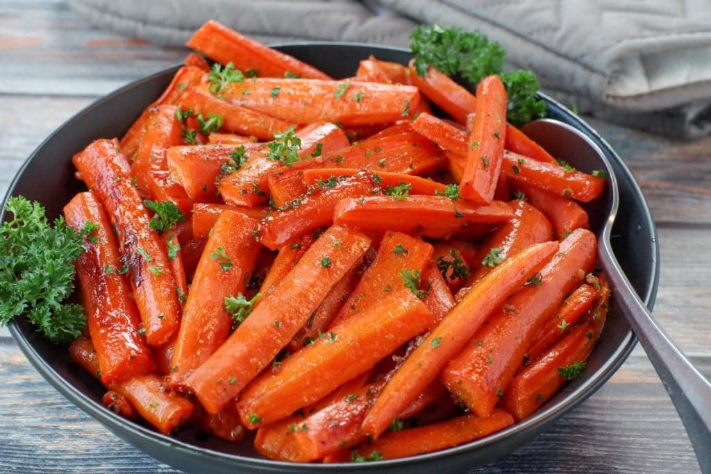 healthy roasted carrots with brown sugar in a black bowl, with a spoon and grey oven mitts in the background