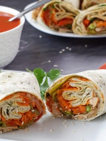 healthy turkey wrap, sliced in half, on white plate, with bowl of tomato soup and platter of turkey wraps in the background