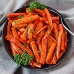 brown sugar glazed carrots in a black bowl, with a spoon, on grey linen