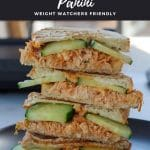 pinterest pin with white text on black background and photo of buffalo chicken panini on a black plate with a panini press in the background