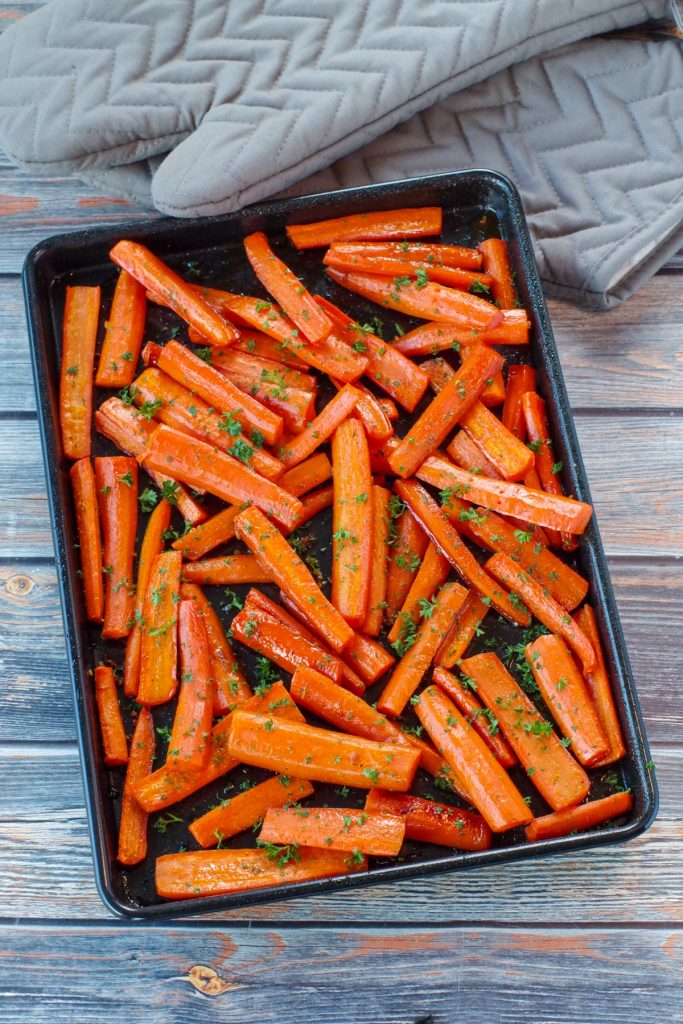 roasted carrots with brown sugar on a black sheet pan on blue faux wood surface